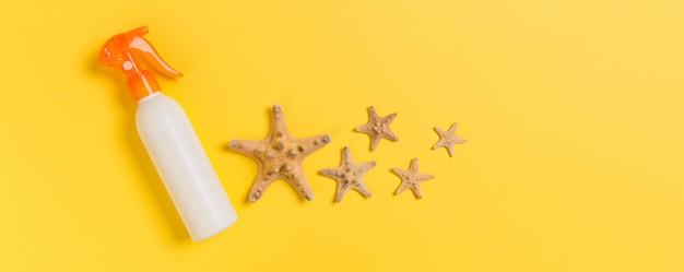 Zonnebrandcrème flessen met schelpen op gele tafel
