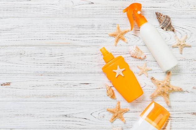 Zonnebrandcrème flessen met schelpen op witte houten tafel