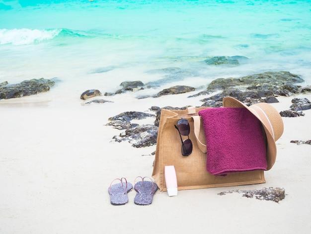 Zonnebrandcrème, hoed, glas, schoenen, handdoek op steen met uitzicht op zee. zomer- en vakantieconcept.