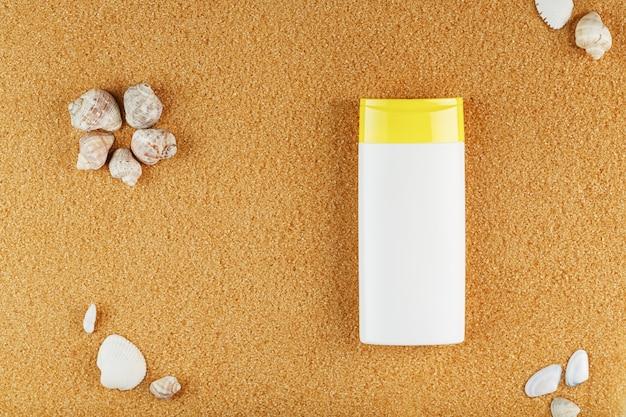 Zonnebrandcrème in een witte fles op het gouden zand met schelpen