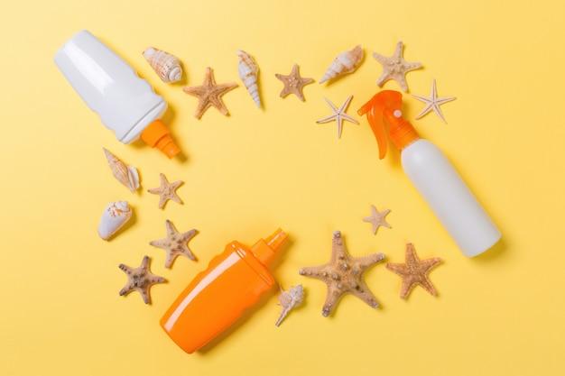 Zonnebrandcrème met zeesterren en schelpen in flessen op geel