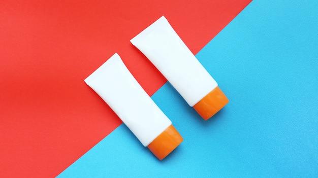 Zonnebrandcrème of cosmetica op oranje gekleurd papier en blauw papier achtergrond