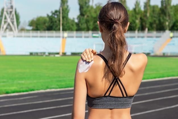 Zonnebrandcrème sunblock. vrouw in een sportkleding die zonneroom op schouder op mooie de zomerdag zet.