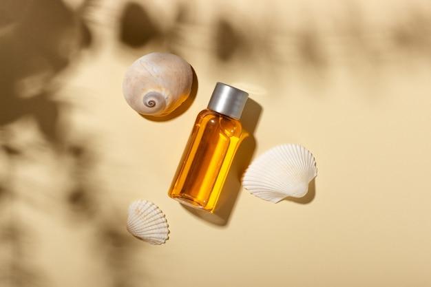 Zonnebrandolie. cosmetische producten naast schelpen in zonnestralen op een roze achtergrond. zonbeschermende cosmetica.