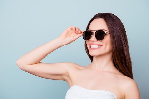 Zonnebril concept. jonge schattige brunette toothy dame in zomer outfit en trendy zonnebril staat op een lichtblauwe ruimte, haar brillen bevestigen. ze is zo stijlvol en aantrekkelijk