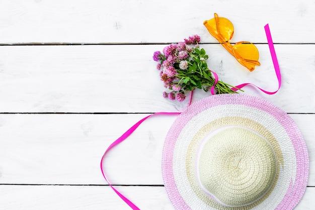 Zonnebril en een strohoed met bloemen