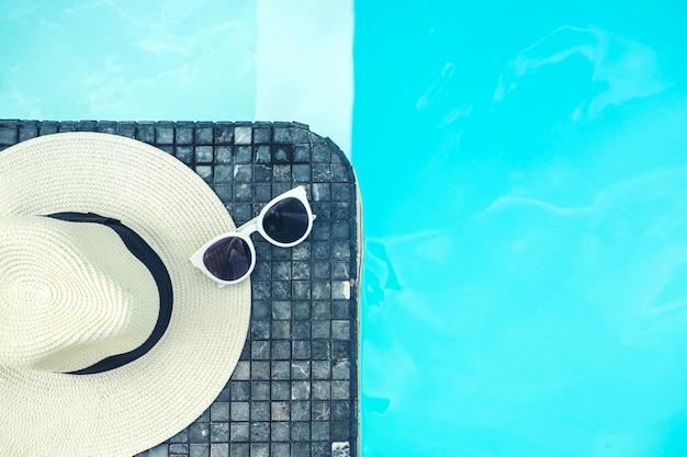 Zonnebril en hoed op het luxueuze tropische strandtoevlucht van het zwembad
