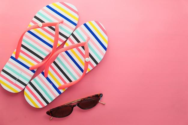 Zonnebril en sandalen op roze achtergrond top down