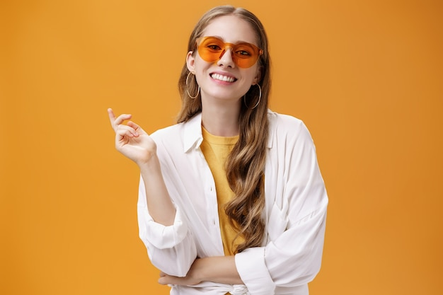 Zonnebril in bijpassende stijl. portret van zelfverzekerde en zorgeloze knappe vrouwelijke modeblogger in brillen en wit t-shirt met opgeheven hand gebarend en vrolijk glimlachend in de camera.