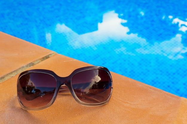 Zonnebril in de buurt van blauw betegeld water van het zwembad