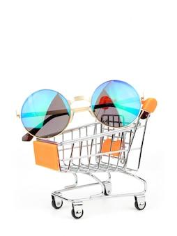 Zonnebril in een boodschappenwagentje, duwkar op witte achtergrond wordt geïsoleerd die. fashion consumption-concept.