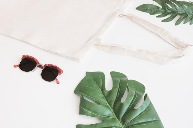 Zonnebril, katoenen zak en groene monstera op witte achtergrond