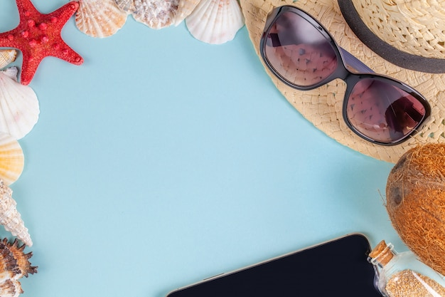 Zonnebril, kokosnoot, zeester, schelpen, strohoed, fles met zand en mobiele telefoon op blauwe achtergrond