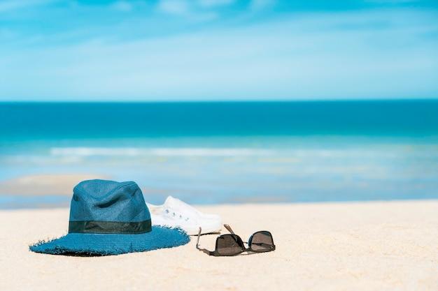 Zonnebril met hoed en schoen op zandstrand