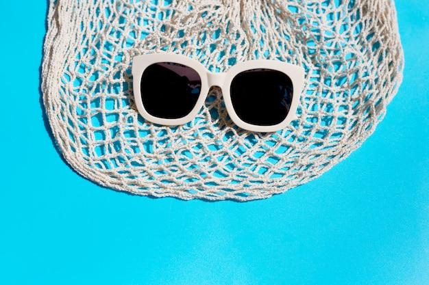 Zonnebril met mesh tas op blauwe achtergrond. geniet van vakantieconcept.