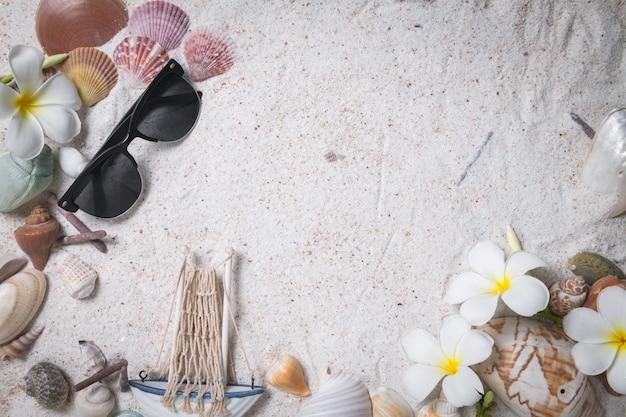 Zonnebril met shells en plumeriabloemen op zandachtergrond