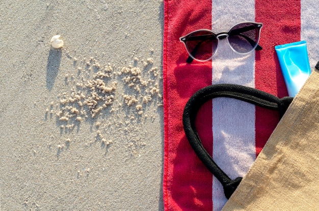 Zonnebril met zonneschermlotion en zak op rode handdoek.
