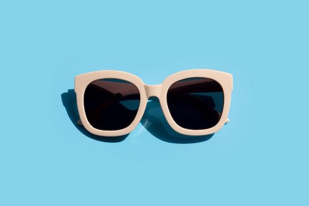 Zonnebril op blauwe achtergrond. geniet van vakantieconcept.