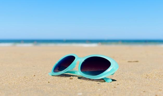 Zonnebril op het strandzand