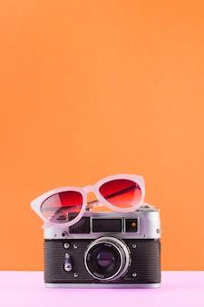 Zonnebril over de uitstekende camera op wit bureau tegen een oranje achtergrond