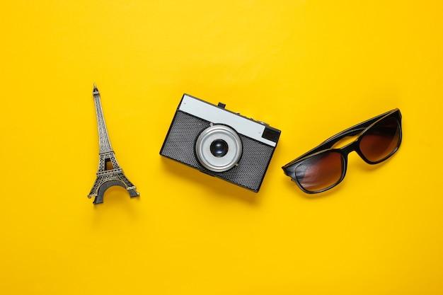 Zonnebril, retro camera, beeldje van de eiffeltoren op gele achtergrond. reis achtergrond. bovenaanzicht