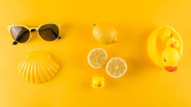 Zonnebril; schulp; citroen en rubberen eend op gele achtergrond