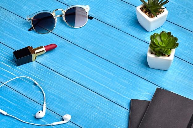 Zonnebril, witte koptelefoon, rode lippenstift, twee zwarte mappen
