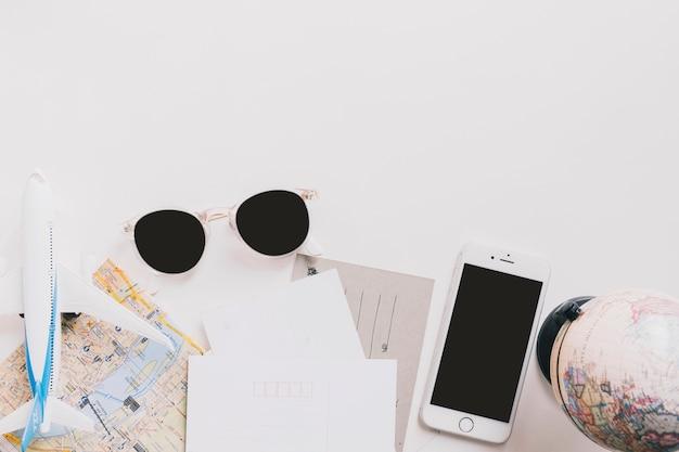 Zonnebrillen en smartphone in de buurt van kaarten