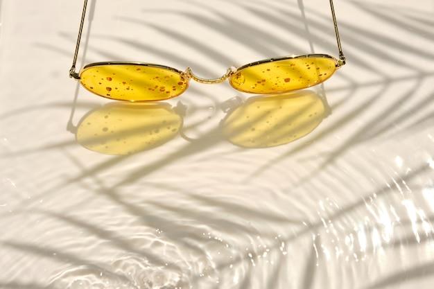 Zonnebrillen in een metalen frame met gele glazen liggen op een heldere waterachtergrond. de schaduw van een palmboom.