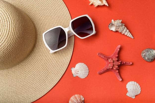 Zonnebrillen, schelpen, een hoed en een zeester. live koraal achtergrond. plat liggen. reizen concept