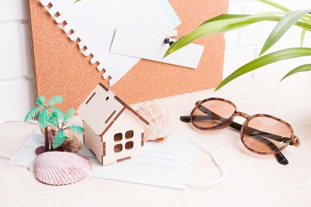 Zonnebrillen, schelpen, kleine palmboom, gezichtsmasker, klein houten huis op het bureaublad, kurkbord op de achtergrond