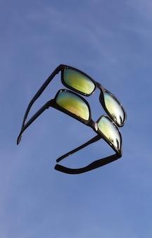 Zonnebrillen worden in de spiegel weerspiegeld tegen de blauwe lucht