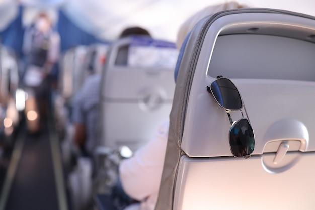Zonnebrillen worden in het vliegtuig op de passagiersstoel geplaatst