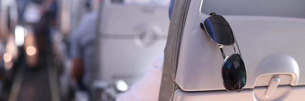 Zonnebrillen worden in het vliegtuig op de passagiersstoel geplaatst.