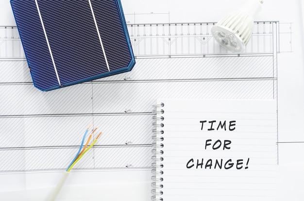 Zonnecellen, draden, ledlamp en notitieblok met teken time for change in een conceptueel beeld van veranderend energiebeleid