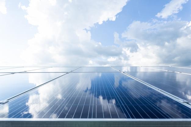 Zonnecellenpaneel op dak met blauwe en bewolkte hemel, groene energie en duurzaam wereldconcept.