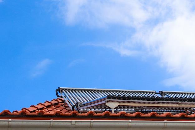 Zonnecollectoren voor warm water en verwarming op het dak van huis op blauwe hemelachtergrond