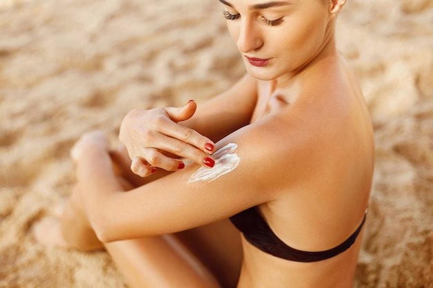 Zonnecreme. huid- en lichaamsverzorging. vrouw die in bikini zonnebrandcrème zonne op gebruinde schouder toepast.