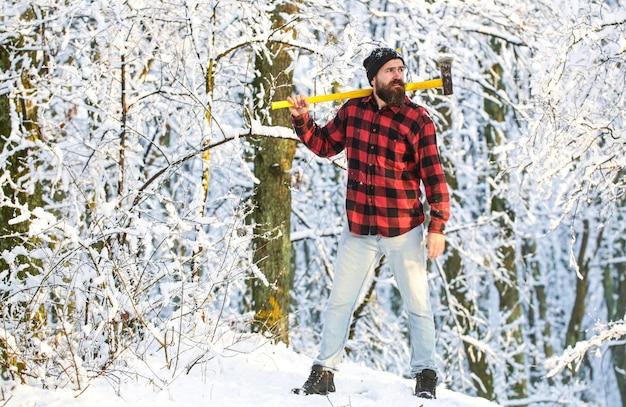 Zonnedag man met bijl in het bos een man in een winterbos houthakker met een bijl in zijn handen bebaarde houthakker