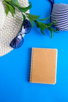 Zonnehoed en bril met een zwempak op een blauwe achtergrond.