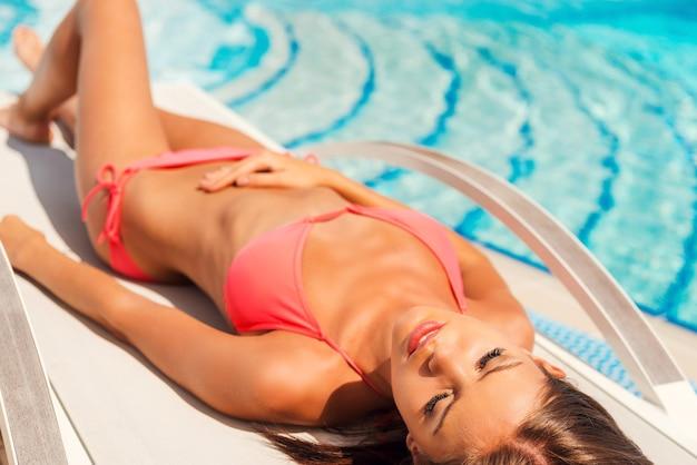 Zonnen bij het zwembad. bovenaanzicht van mooie jonge vrouw in bikini liggend op een ligstoel bij het zwembad