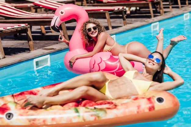 Zonnen. prachtige jonge meisjes in badkleding glimlachen terwijl ze drijven op de opblaasbare ring in het zwembad.