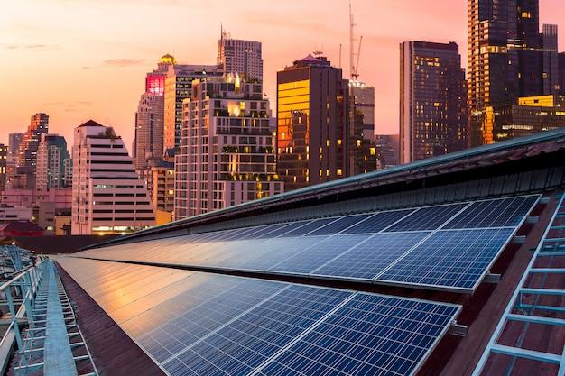 Zonnepaneel fotovoltaïsche installatie op een dak van fabriek, zonnige blauwe hemelachtergrond, alternatieve elektriciteitsbron - duurzaam hulpbronnenconcept.