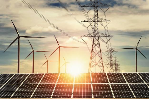 Zonnepaneel met turbine en torenhoogspanning zonsondergang