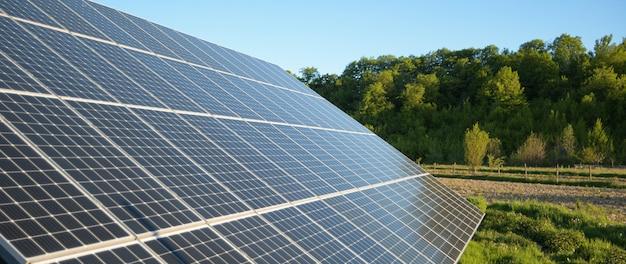 Zonnepaneel tegen blauwe hemelachtergrond. fotovoltaïsche, alternatieve elektriciteitsbron. idee voor duurzame hulpbronnen. alternatief energieconcept. zonneboerderij op groen gras