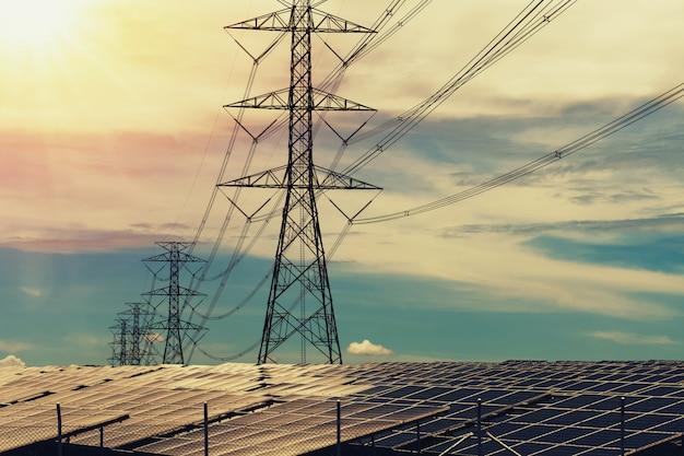 Zonnepanelen met hoogspanningsmast en zonsondergang. schoon energieconcept