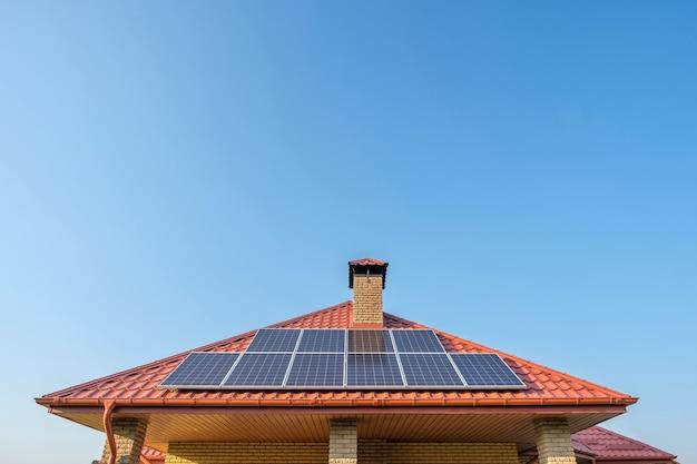 Zonnepanelen op het dak van een woonhuis op blauwe hemelachtergrond