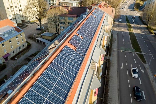 Zonnepanelen systeem op hoog dak van appartementencomplex.