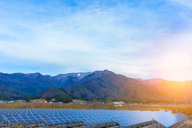 Zonnepanelen (zonnecel) in zonnelandbouwbedrijf met blauwe hemel en zonverlichting.