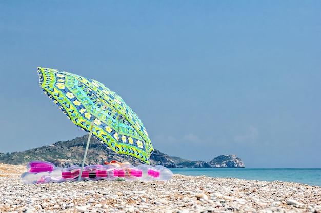 Zonnescherm en luchtbed op het strand